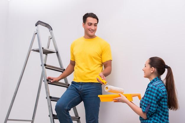 Pareja joven pintando la pared en casa