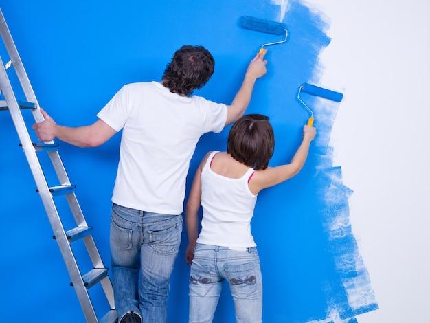 Pareja joven pintando la pared con rodillo juntos