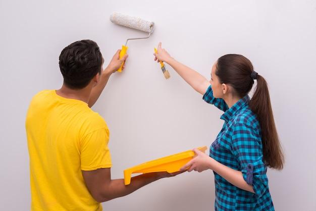 Pareja joven pintura pared en casa