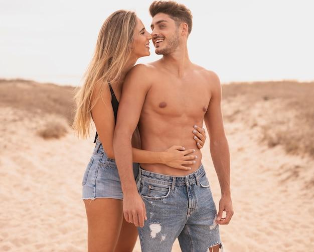 Pareja joven en la playa abrazando