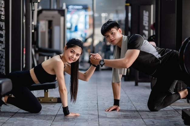 Pareja joven posan con la mano y mostrando músculos fuertes del brazo juntos en el gimnasio moderno,