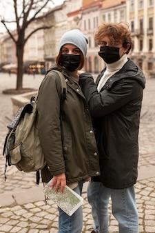 Pareja joven posando al aire libre con máscaras médicas