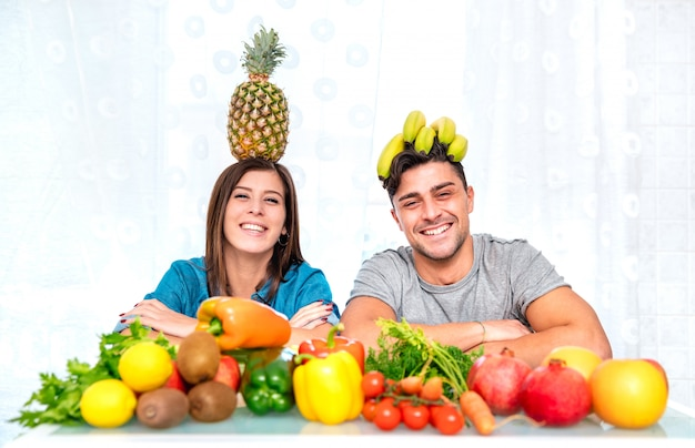 Pareja joven posando en casa cocina con comida vegetariana saludable y fruta