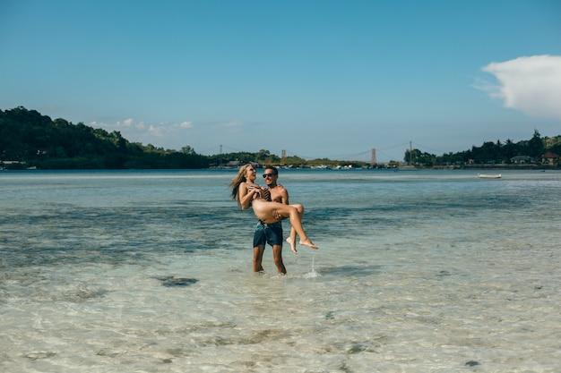 Pareja joven posando en la playa, divirtiéndose en el mar, riendo y sonriendo