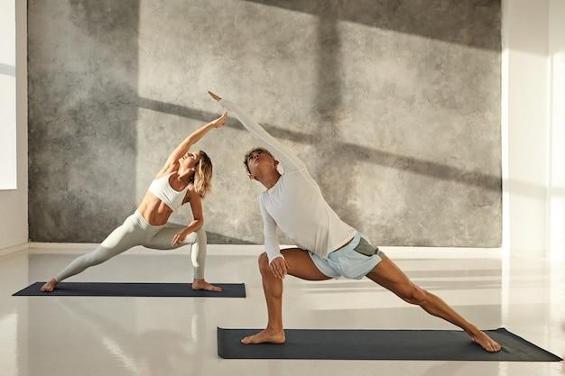 Pareja joven practicando yoga juntos. imagen interior de un guapo chico bronceado sobre una alfombra haciendo poses de pie para fortalecer las piernas, estirar los brazos y mirar hacia arriba