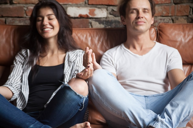 Pareja joven practicando yoga meditando juntos en casa en sofá