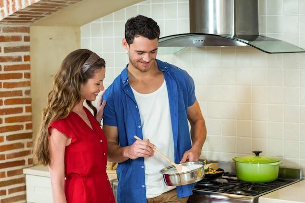 Pareja joven preparando la comida juntos en la cocina en casa