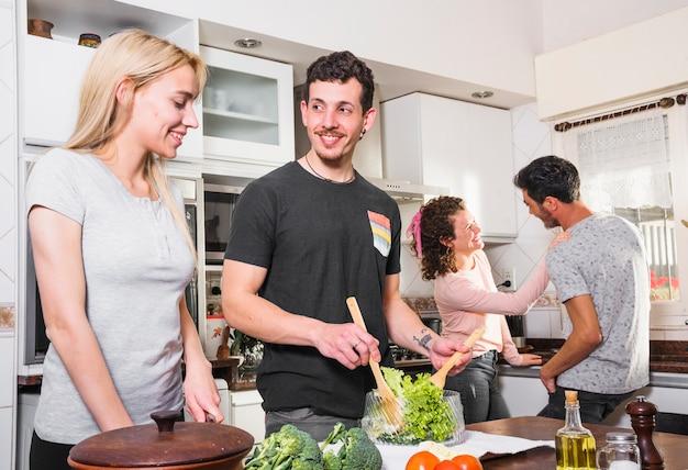 Pareja joven preparando ensalada y sus amigos hablando entre sí en el fondo en la cocina