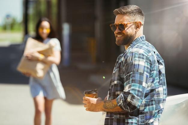 Pareja joven preparándose para el viaje de vacaciones en el coche en un día soleado. mujer y hombre de compras y listo para ir al mar, a la orilla del río o al océano.