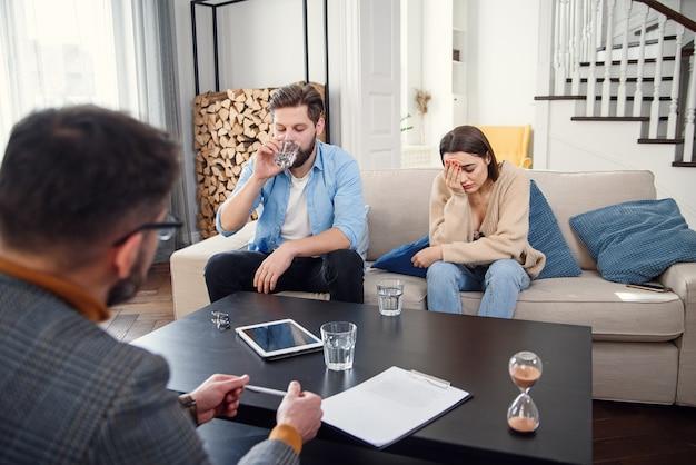 Pareja joven con problemas en la recepción para psicólogo familiar.