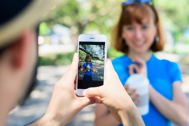 Pareja joven que toma la foto con la cámara del teléfono inteligente.