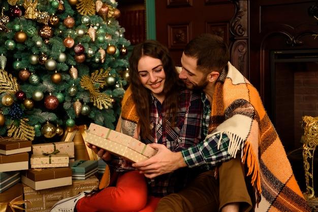 Pareja joven con regalos cerca del árbol de navidad