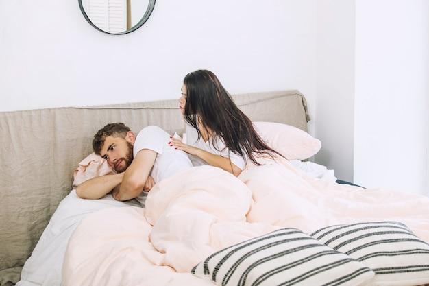 Pareja joven en una relación un hombre y una mujer juran una casa triste en el dormitorio en la cama