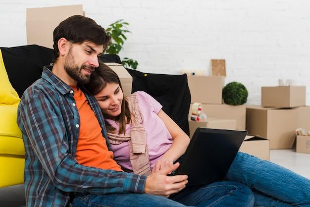 Pareja joven relajada romántica en casa moderna usando laptop