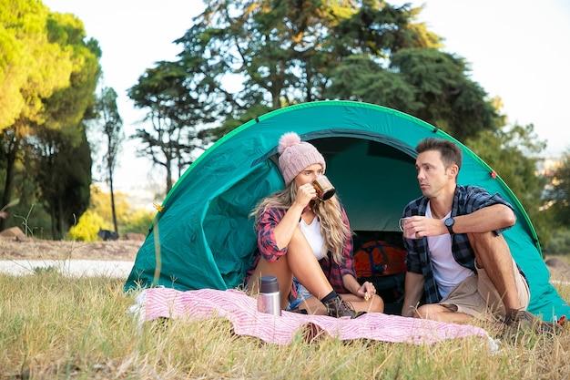Pareja joven relajándose en la naturaleza juntos y bebiendo té. mujer caucásica de pelo largo con sombrero sentado en la tienda junto con el hombre y charlando. concepto de turismo, aventura y vacaciones de verano.