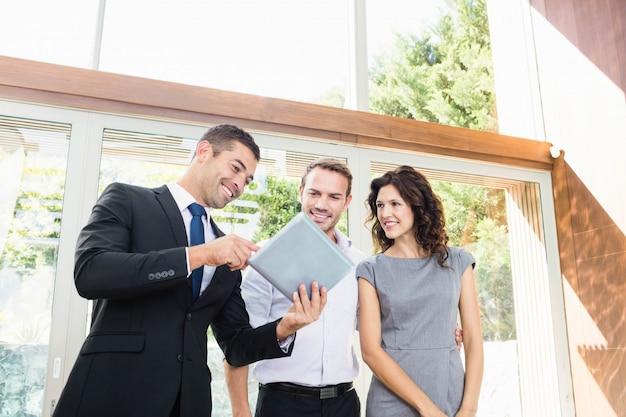 Pareja joven reunión inmobiliaria mostrando un proyecto de casa en una tableta digital