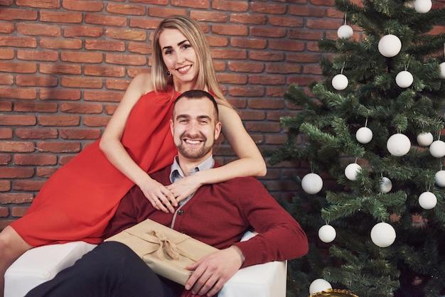 Pareja joven reunión navidad abrazando a casa. año nuevo. humor festivo de un hombre y una mujer.