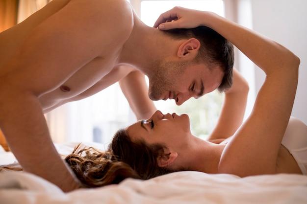 Pareja joven romántica acostada en la cama con cuerpos en direcciones opuestas mientras se besa