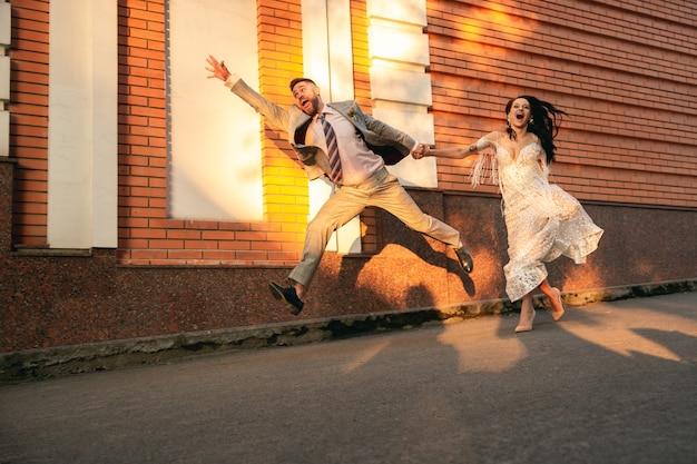 Pareja joven romántica caucásica celebrando el matrimonio en la ciudad.