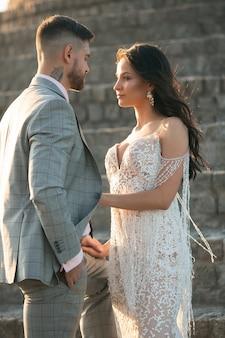 Pareja joven romántica caucásica celebrando su matrimonio en la ciudad. tierna novia y el novio en la calle de la ciudad moderna. familia, relación, concepto de amor