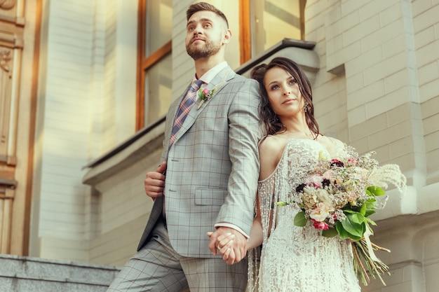 Pareja joven romántica caucásica celebrando su matrimonio en la ciudad.