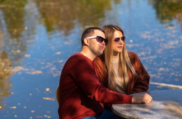 Pareja joven romántica que data en un parque de otoño sentado en una mesa en un restaurante al aire libre con vistas a un lago