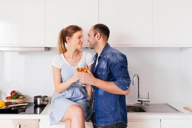 Pareja joven romántica sosteniendo copas en la mano mirando el uno al otro