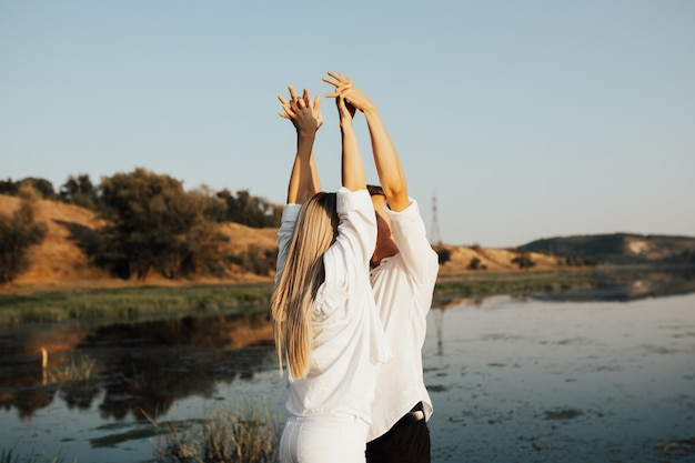 Pareja joven en ropa blanca cerca del río levantando las manos. río y colinas