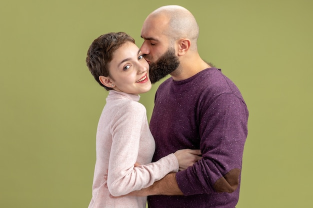 Pareja joven en ropa casual mujer con pelo corto y hombre barbudo feliz enamorado juntos hombre besando a su novia celebrando el día de san valentín de pie sobre la pared verde