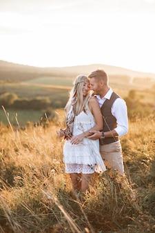 Pareja joven en ropa rústica boho elegante abrazando, de pie en el campo al atardecer