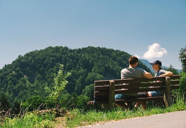 Pareja joven sentada en un banco de madera en una ladera cubierta de hierba verde disfrutando de la vista panorámica de los alpes