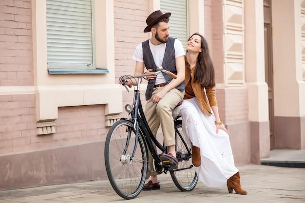 Pareja joven sentada en una bicicleta contra la pared