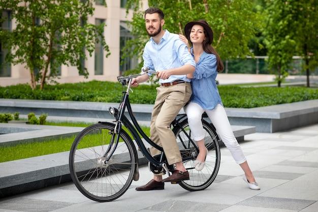 Pareja joven sentada en una bicicleta frente al parque verde de la ciudad