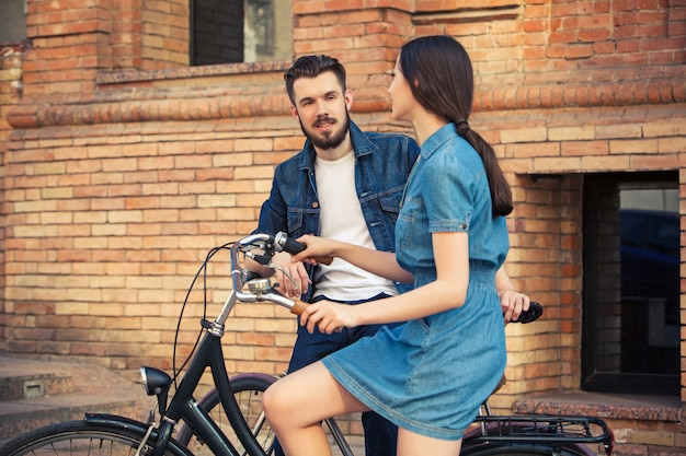 Pareja joven sentada en una bicicleta frente a la ciudad