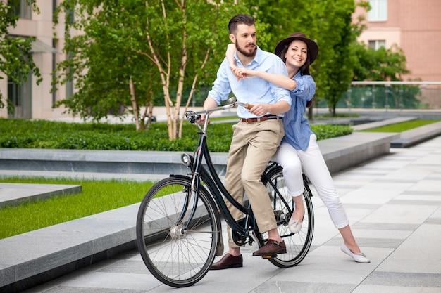 Pareja joven sentada en una bicicleta