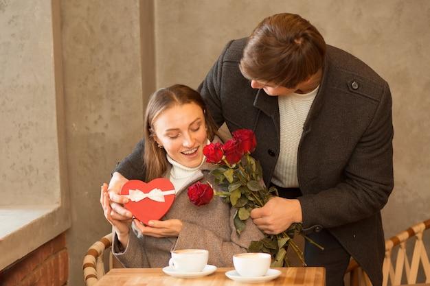 Pareja joven sentada en caffe con café, caja de regalo de corazón y ramo de rosas. novio haciendo sorpresa a su novia. día de san valentín. foto de alta calidad