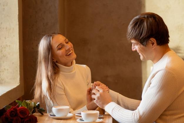 Pareja joven sentada en caffe con café y ramo de rosas. día de san valentín. foto de alta calidad