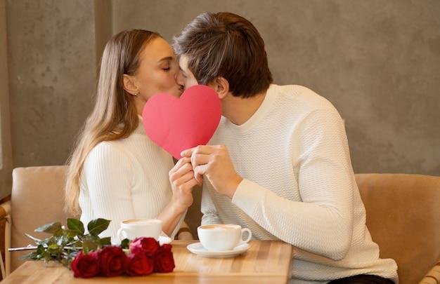 Pareja joven sentada en caffe con café, ramo de rosas, sosteniendo corazón de papel. novio haciendo sorpresa a su novia. día de san valentín. foto de alta calidad