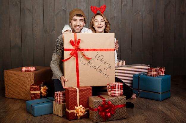 Pareja joven sentada entre cajas de regalo de navidad sobre superficie de madera