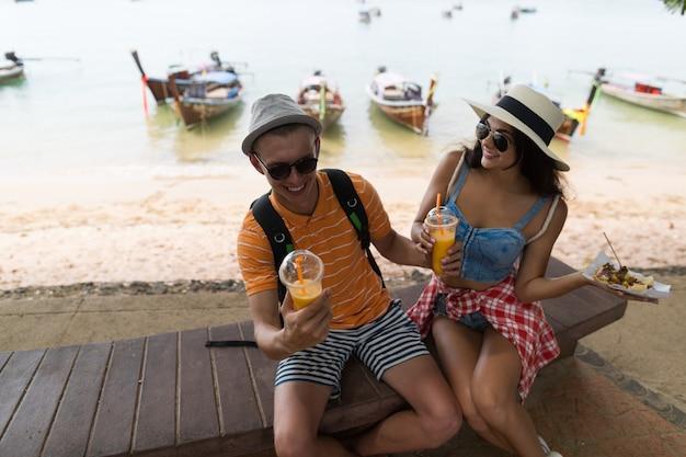 Pareja joven sentada cerca de la playa comiendo comida callejera y bebiendo jugo fresco