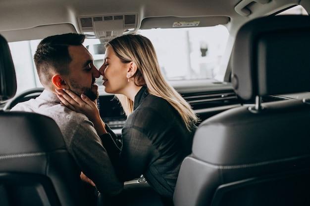 Pareja joven sentada en el coche y besándose