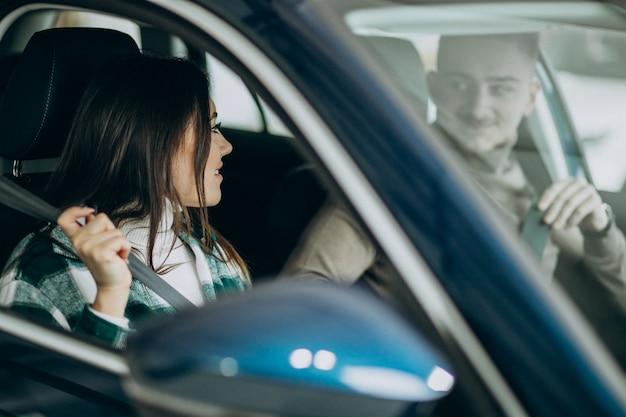 Pareja joven sentada en el coche en una sala de exposición de automóviles
