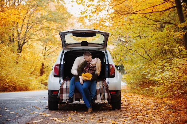 Pareja joven sentada en el maletero de un coche en la carretera en otoño