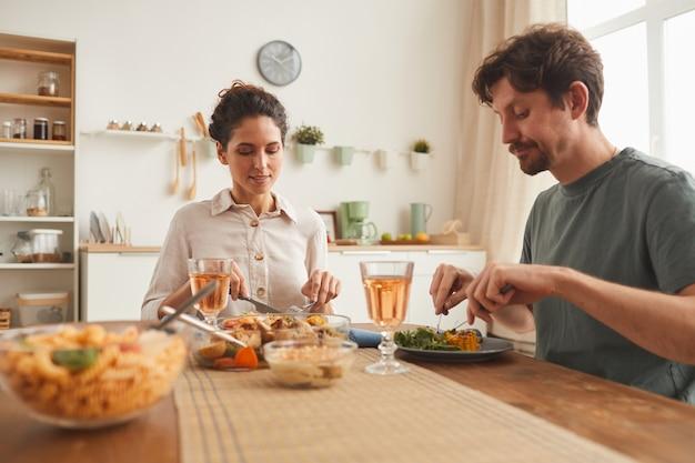 Pareja joven sentada a la mesa y disfrutando de una cena juntos en la cocina doméstica