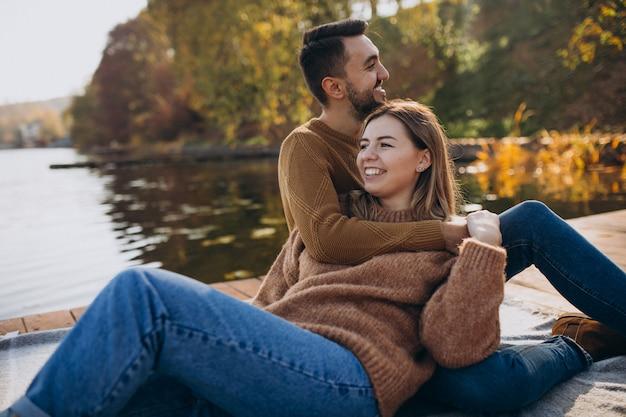 Pareja joven sentada en el puente de cubierta junto al río