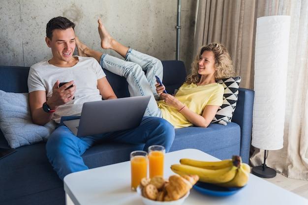 Pareja joven sentada en el sofá en casa con teléfonos inteligentes
