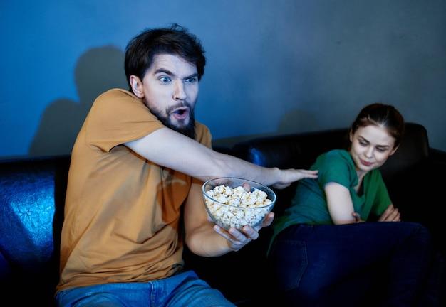 Pareja joven sentada en el sofá por la noche viendo la televisión descanso de palomitas de maíz