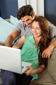 Pareja joven sentada en el sofá y usando laptop