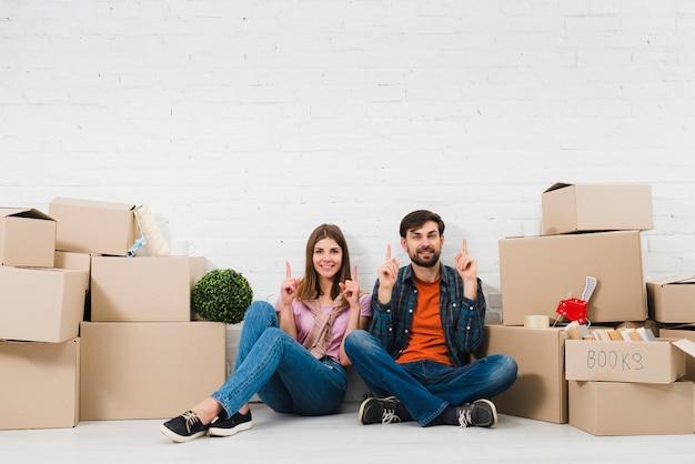 Pareja joven sentada en el suelo sosteniendo sus dedos hacia arriba, sentada entre las cajas de cartón
