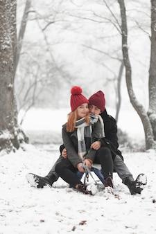 Pareja joven sentada en trineo y jugando con nieve